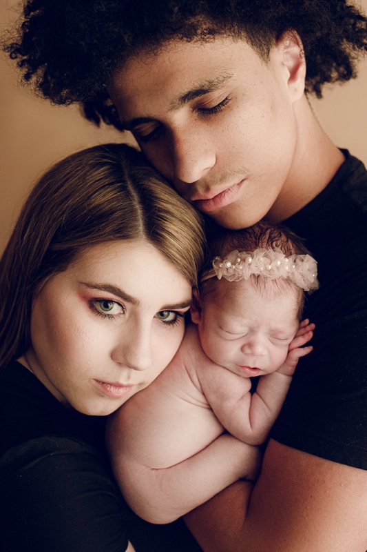 Portrait Studio in Louisville KY, mother and father with newborn baby cuddled up between them