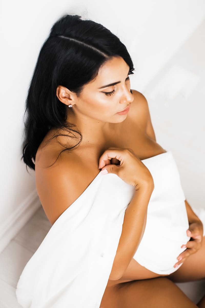 Portrait Studio in Louisville KY, woman draped in white, sitting against white wall