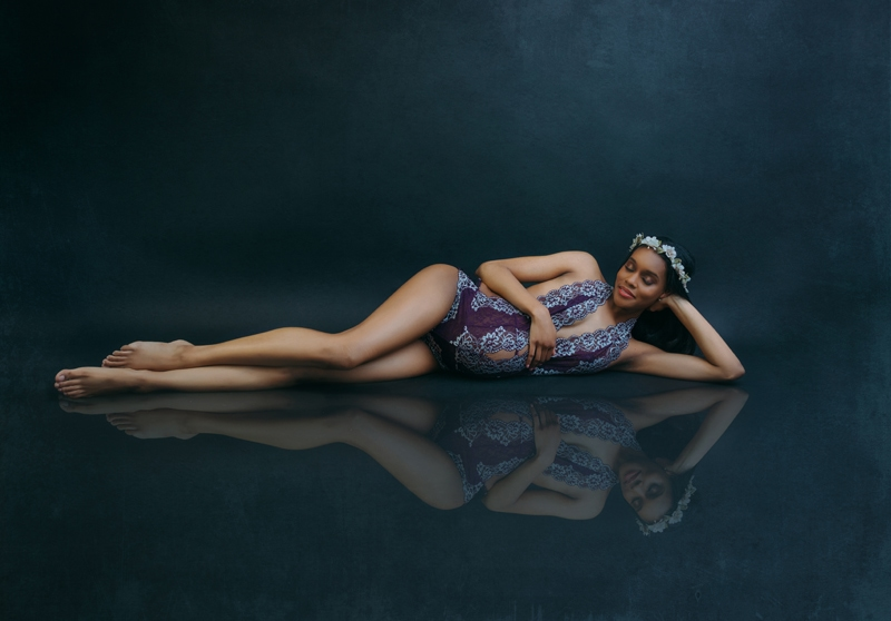 Portrait Studio in Louisville KY, woman laying on a blue background with floral crown