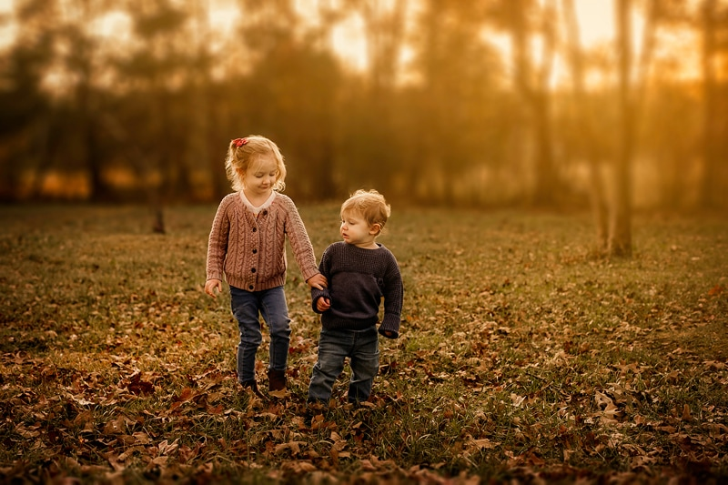 Portrait Studio in Louisville KY, young sister and brother walking hand in hand