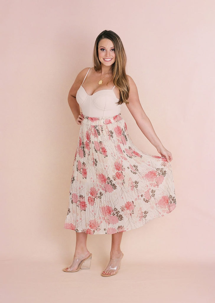 Woman in pink floral dress posing for glamour photoshoot