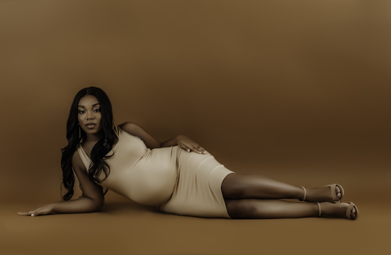 Louisville Maternity Photographer, woman laying down on brown backdrop